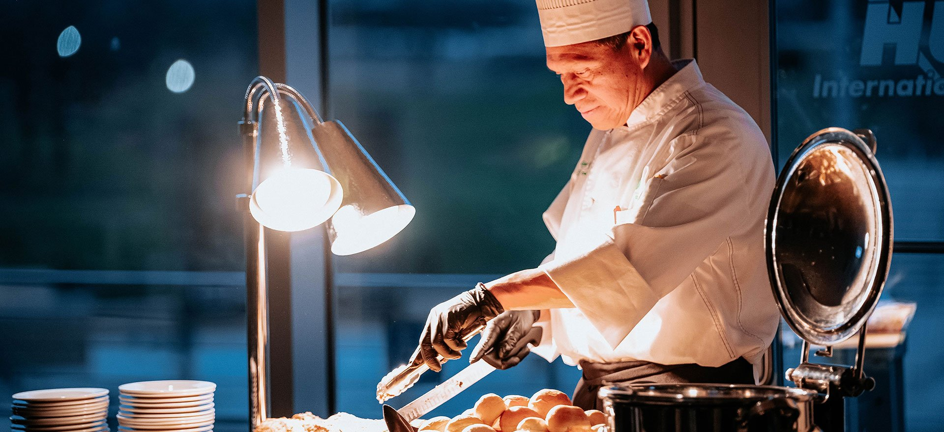 Artisan chef carves meat at a catering event